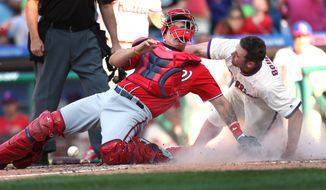Philadelphia Phillies' Peter Bourjos, right, is safe at home after colliding with Washington Nationals catcher Jose Lobaton, left, to score on a single by Andres Blanco in the 10th inning of a baseball game, Sunday, April 17, 2016, in Philadelphia. The Phillies won 3-2. (AP Photo/Laurence Kesterson)