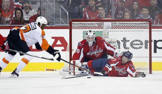 Washington Capitals defenseman Karl Alzner (27) lies on the ice to block a shot by Philadelphia Flyers right wing Wayne Simmonds (17) with Washington Capitals goalie Braden Holtby (70) behind, during the second period of Game 2 in the first round of the NHL Stanley Cup hockey playoffs, Saturday, April 16, 2016, in Washington. (AP Photo/Alex Brandon)