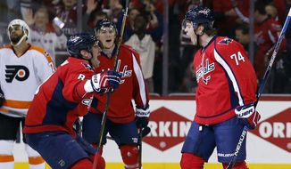 Washington Capitals left wing Alex Ovechkin (8), from Russia, and defenseman John Carlson (74) celebrate after Carlson's goal during the first period of Game 2 in the first round of the NHL Stanley Cup hockey playoffs against the Philadelphia Flyers, Saturday, April 16, 2016, in Washington. (AP Photo/Alex Brandon)