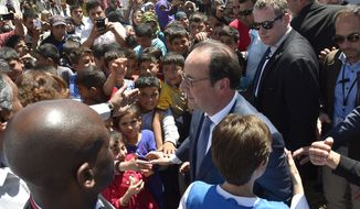 In this photo released by Lebanon's official government photographer Dalati Nohra, Syrian refugee children shake hands with French President Francois Hollande, center, during his visit to their informal refugee camp, in Dalhamyeh village, in the eastern Bekaa valley, Lebanon, Sunday, April 17, 2016. Hollande arrived in Beirut Saturday at the start of a regional tour that will take him to Egypt and Jordan. During his two-day visit to Lebanon, the French president is scheduled to meet senior officials and visit a group of Syrian refugees in the country's eastern Bekaa Valley. (Dalati Nohra via AP)