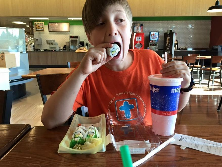CORRECTS DATE TO SATURDAY - In this Saturday, April 16, 2016 photo provided by Kristen Moore, her son Fletcher Moore eats sushi at a Meijer store in Grand Rapids, Mich. The 9-year-old had a party and spent nine hours at the store to celebrate his birthday. (Kristen Moore via AP)