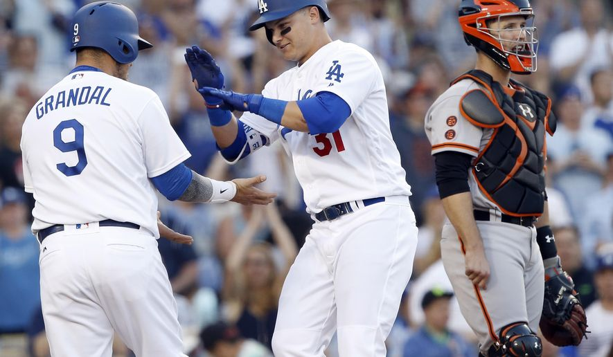 Los Angeles Dodgers' Joc Pederson, center, gets congratulations from Yasmani Grandal after hitting a two-run home run, as San Francisco Giants catcher Buster Posey looks away, during the fifth inning of a baseball game in Los Angeles, Sunday, April 17, 2016. (AP Photo/Alex Gallardo)