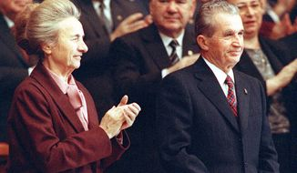 Romanian government leader Nicolae Ceausescu receives applause at the last convention of communist party in November 1989. At left is his wife, Elena. (Associated Press)