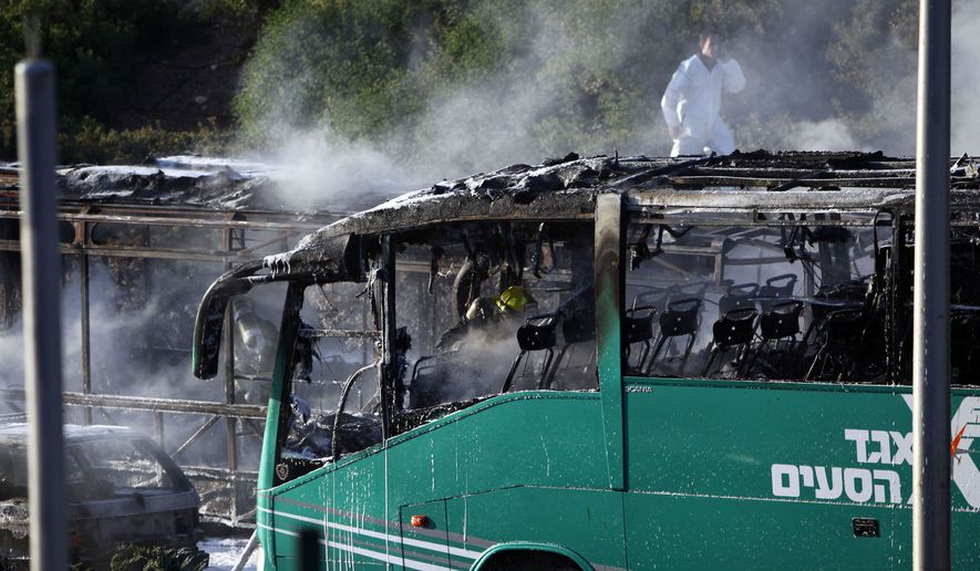 An Israeli firefighter is seen inside a burnt bus in Jerusalem, Monday, April 18, 2016.  A bus exploded in the heart of Jerusalem Monday, wounding at least 15 people who appeared to have been in an adjacent bus that was also damaged. The explosion raised fears of a return to the Palestinian suicide attacks that ravaged Israeli cities a decade ago. (AP Photo/Mahmoud Illean)