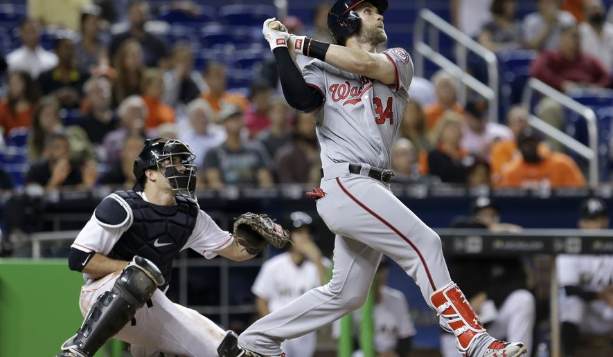Washington Nationals' Bryce Harper (34) follows through on a sacrifice fly against the Miami Marlins during the fifth inning of a baseball game, Monday, April 18, 2016, in Miami. Washington Nationals center fielder Michael Taylor (3) scored on the sacrifice fly. (AP Photo/Alan Diaz)