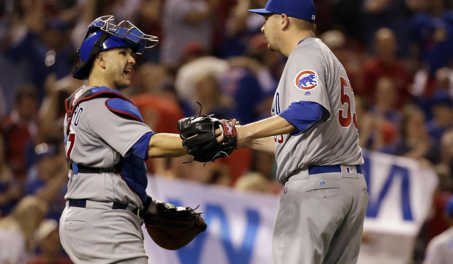 Chicago Cubs relief pitcher Trevor Cahill, right, and catcher Miguel Montero celebrate winning a baseball game against the St. Louis Cardinals on Monday, April 18, 2016, in St. Louis. The Cubs won 5-0. (AP Photo/Jeff Roberson)