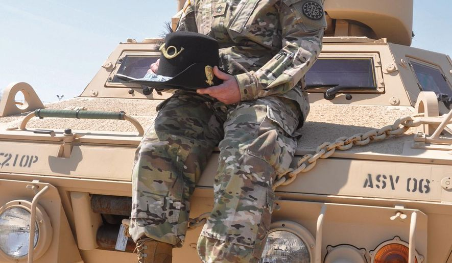 In this April 14, 2016 photo, Sfc. Billy Adrian, administrative leader of the 144th Military Police Company, nicknamed the Blackhats, sits atop an Armored Security Vehicle at the unit's headquarters in Corunna, Mich. The 144th's unit number and flag have been reassigned to Nebraska. (Sally York/The Argus-Press via AP) MANDATORY CREDIT