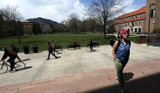 In this April 20, 2015 file photo, students walk to and from classes on the campus quad of the University of Colorado, in Boulder, Colo. There's good news and bad news in the $27 billion state budget up for debate Thursday, March 31, 2016, in the Colorado House. Schools and colleges aren't getting budget cuts. Colleges and vocational training programs fared well, too, getting an extra $14.5 million despite warnings from legislative Democrats that Colorado's 31 public institutions of higher education would see budget cuts requiring tuition hikes. (AP Photo/Brennan Linsley, File) — FILE