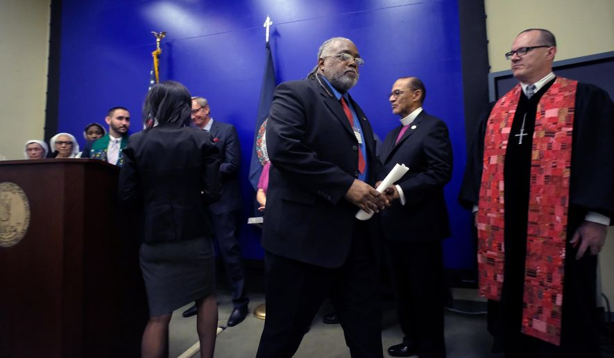 Death row exoneree Harold Wilson, thrid from right, leaves the podium after adressing a press conference at the General Assembly Building in Richmond, Va., Monday, April 18, 2016, with faith leaders opposed to the death penalty. The group of religious leaders is denouncing Virginia Gov. Terry McAuliffe's effort to shield the identities of pharmacies that supply drugs for executions. Two of those participating were Bishop Carroll Baltimore, Immediate National Past President, PNBC, second from right, and Rev. Max Blalock, William & Mary Wesley Foundation, right. (Bob Brown/Richmond Times-Dispatch via AP).