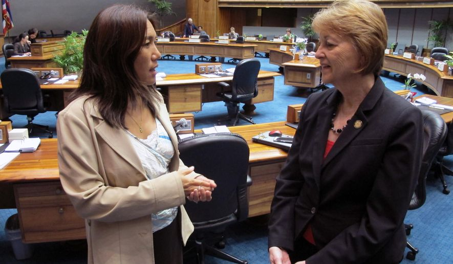 Hawaii State Senators Maile Shimabukuro, left, and Roz Baker, right, talk on the Senate floor on Monday, April 18, 2016, in Honolulu. Breastfeeding moms could soon be exempt from jury duty in Hawaii under a bill passed by the Hawaii Legislature. The state Senate passed a bill Monday that would give the exemption to mothers who are breastfeeding children up to two years old. (AP Photo/Cathy Bussewitz)