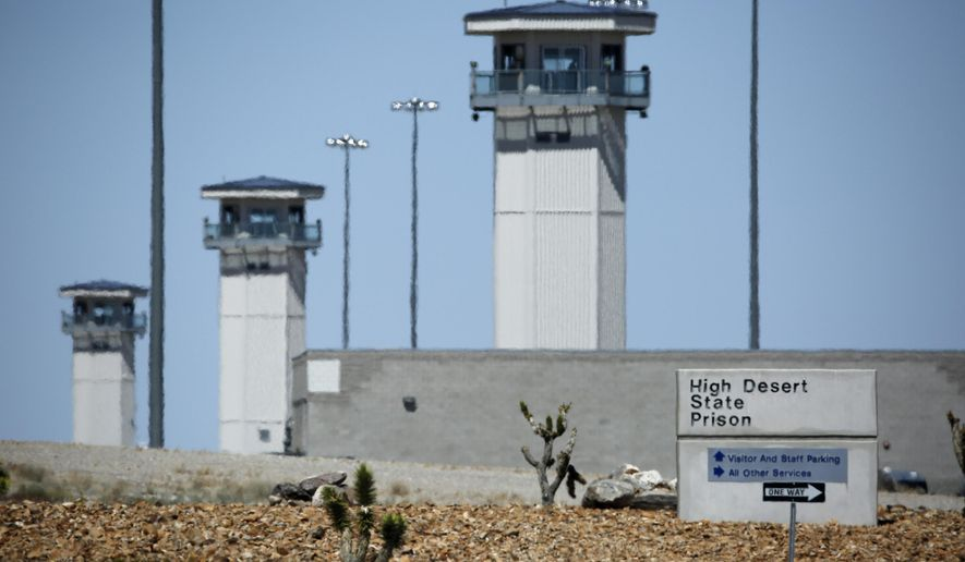 FILE - In this April 15, 2015, file photo, guard towers are seen at High Desert State Prison in Indian Springs, Nev. The Nevada state attorney general on Monday, April 18, 2016, charged a former prison guard trainee with involuntary manslaughter in the shotgun killing of a handcuffed inmate in a prison hallway in Nov. 2014. (AP Photo/John Locher, File)