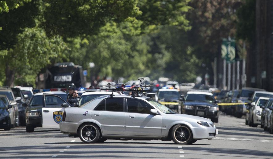 A man barricades himself in his car while blocking an intersection on the north side of the state Capitol Monday, April 18, 2016 in Sacramento, Calif. A standoff near the California Capitol is over after a vehicle covered in scribbled writing blocked traffic and stalled business for several hours. Sacramento police said a suspect in a suspicious car voluntarily surrendered Monday. (Randy Pench/The Sacramento Bee via AP)  MAGS OUT; LOCAL TELEVISION OUT (KCRA3, KXTV10, KOVR13, KUVS19, KMAZ31, KTXL40); MANDATORY CREDIT
