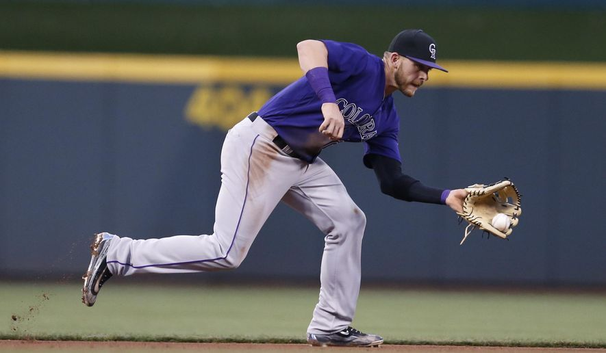 Colorado Rockies shortstop Trevor Story fields a ground ball off the bat of Cincinnati Reds' Brandon Phillips during the fourth inning of a baseball game, Monday, April 18, 2016, in Cincinnati. (AP Photo/Gary Landers)