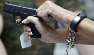 Sally Abrahamsen (right), of Pompano Beach, Fla., holds a Glock 42 pistol while shopping for a gun at the National Armory gun store and gun range in Pompano Beach on Jan. 5, 2016. At left is salesperson T.J. O'Reilly. (Associated Press) **FILE**