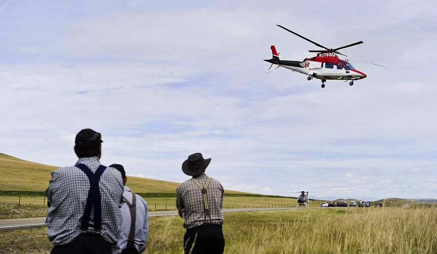 In this July 15, 2015 photo, an emergency helicopter flies over the scene of a fatal collision on Highway 287, north of Wolf Creek, Mont. Air ambulances are life-savers for many people who live in rural states such as Montana, but as the industry has grown, so too have complaints about soaring bills and the lack of regulations over the sudden influx of private companies that provide helicopter and fixed-wing emergency services. (Thom Bridge/Independent Record via AP) MANDATORY CREDIT