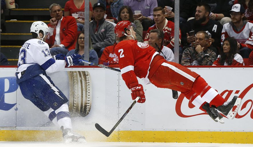 Detroit Red Wings defenseman Brendan Smith (2) is checked by Tampa Bay Lightning center Cedric Paquette (13) during the second period of Game 4 in a first-round NHL hockey Stanley Cup playoff series, Tuesday, April 19, 2016, in Detroit. (AP Photo/Paul Sancya)