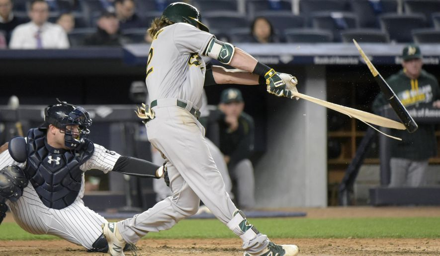 Oakland Athletics' Josh Reddick breaks his bat while flying out as New York Yankees catcher Brian McCann watches during the fifth inning of a baseball game Tuesday, April 19, 2016, at Yankee Stadium in New York. (AP Photo/Bill Kostroun)