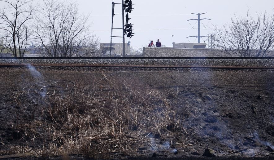 "Men look over a burned area after officials put out a brush fire along a rail line, Tuesday, April 19, 2016, in Secaucus, N.J. The fire in Kearny and Secaucus caused disruptions to rail service. Both blazes sent large clouds of thick, black smoke billowing into the air, but no injuries were reported. The National Weather Service has issued a ""red flag"" warning, saying strong winds and dryness are creating ideal conditions for brush fires. (AP Photo/Julio Cortez)"