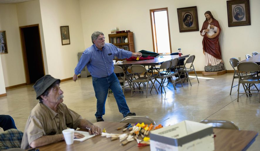 In this April 2, 2016 photo, Alan Smallwood, of Bourbonnais, Ill., throws a dart while John Lurgio, of L'Erable, Ill., left, keeps score in a game of dartball in the parish hall of St. John the Baptist Church in L'Erable. The objective is to hurl 10-inch darts at a board 25 feet away. When they stick, they count as balls, strikes, outs or any of the hits that count in a normal game of baseball. (Nicholas Holstein/The Daily Journal via AP) MANDATORY CREDIT