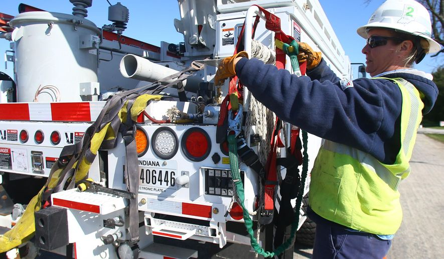 Duke Energy Lineman Karrie Welker, who is in her second year of apprenticeship, works with 7200 volt lines as her and the crew she is with change a utility pole and add a transformer for new service near Sharpsville, Ind., on April 14, 2016. Welker, 41, is soon to be the only active female line worker employed by Duke Energy in Indiana. (Tim Bath/Kokomo Tribune via AP)