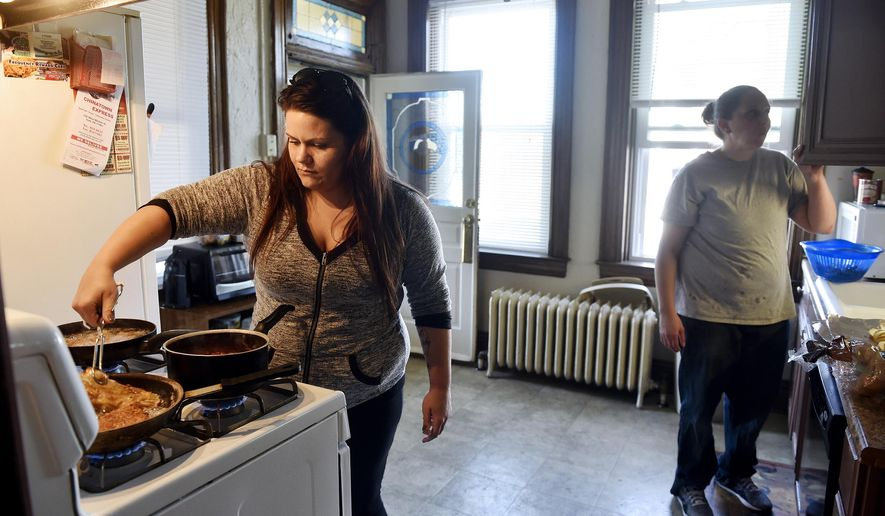In this March 7, 2016 photo, Christina Whelan makes chicken parmesan with help from Allison Foust at the Pennsylvania Avenue house where they live and which is operated by Choices Recovery House. Recovery homes, which give people a place to stay while trying to get sober, have rules but are unregulated. Some acknowledge that the home are part of the recovery process but wonder if state regulation would help their accountability, but others say they aren't intended to be treatment centers and shouldn't be regulated as such. (Chris Dunn/York Daily Record via AP)  YORK DISPATCH OUT; MANDATORY CREDIT