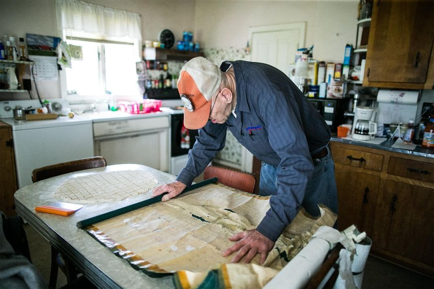 ADVANCE FOR SATURDAY, APRIL 23 AND THEREAFTER - In an April 13, 2016 photo, Newport Cemetery caretaker Charlie Wentz looks for a name on one of the old maps of the cemetery that often were hand-drawn on the backs of window blinds. The Newport Cemetery recently digitized their grave records.  (Sean Simmers/PennLive.com via AP)