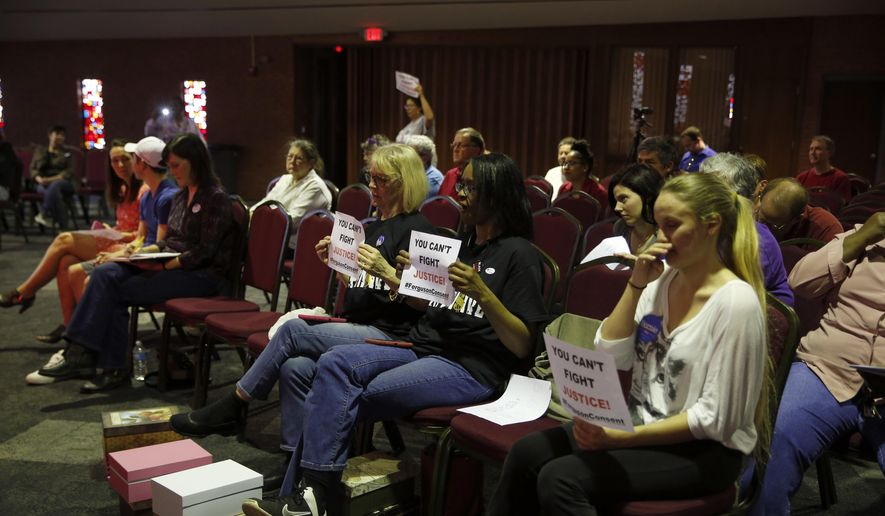 In this March 15, 2016, file photo, people watch and hold signs as members of the Ferguson City Council meet in Ferguson, Mo. St. Louis-area residents were sounding off Tuesday, April 19, 2016 in the last public hearing on the U.S. Department of Justice's settlement that calls for sweeping changes in Ferguson, where 18-year-old Michael Brown was fatally shot by a police officer. (AP Photo/Jeff Roberson, File)