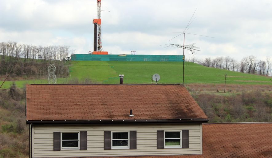 This April 1, 2016, photo shows a private home, foreground, with a shale gas drilling rig in the background, in Washington, Pa. Only 17 rigs are actively exploring in Pennsylvania, down from a high of 115 in 2011 and the fewest since December 2007, amid a prolonged industry slump. (AP Photo/Michael Rubinkam)