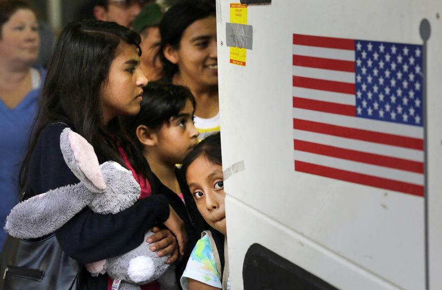 FILE - In this July 7, 2015 file photo, immigrants from El Salvador and Guatemala who entered the country illegally board a bus after they were released from a family detention center in San Antonio, Texas. The vast majority of immigrant children who arrive alone at the U.S. border are placed by the government with adults who are in the country illegally, federal data reviewed by The Associated Press show. (AP Photo/Eric Gay, File)