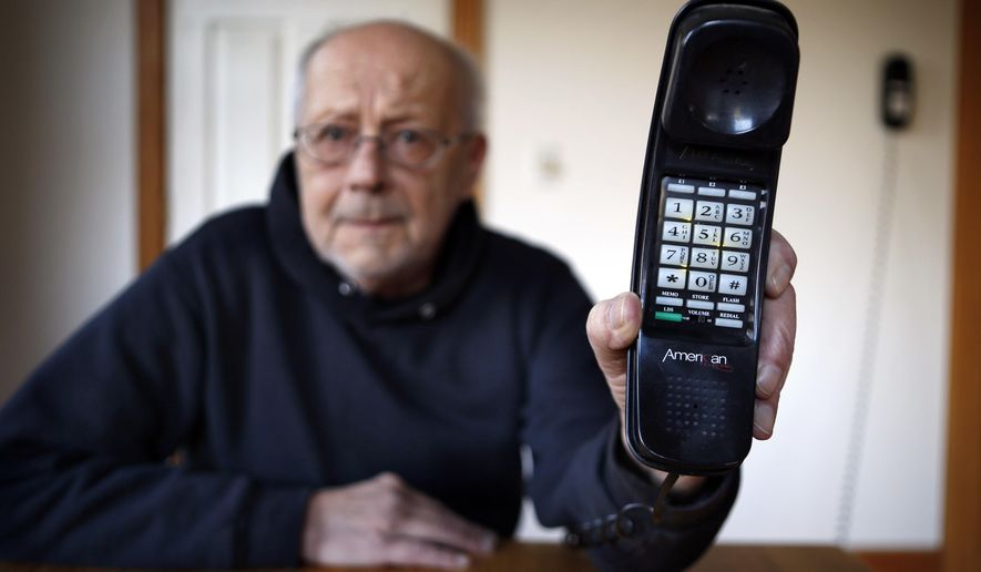In this Wednesday, April 14, 2016 photo, Peter Froehlich holds the landline telephone he uses at his rural home in Whitefield, Maine. Across the country, telecom companies are lobbying lawmakers to be released from their mandate of providing service to every home. (AP Photo/Robert F. Bukaty)