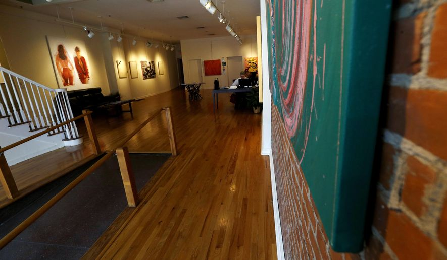 Artwork, left, by painter Tom Dash, depicting a partially a nude woman, hangs at Borghi Fine Art Gallery in Englewood, N.J., Tuesday, April 19, 2016. The gallery has filed a federal lawsuit arguing that its constitutional rights were violated when it was fined $1,250 per day and the owner, Laura Borghi, was threatened with up to 90 days in jail over the artwork, which shows a woman's bare buttocks. A city code says nude images have to be kept in interior rooms not visible from public areas. (AP Photo/Julio Cortez)