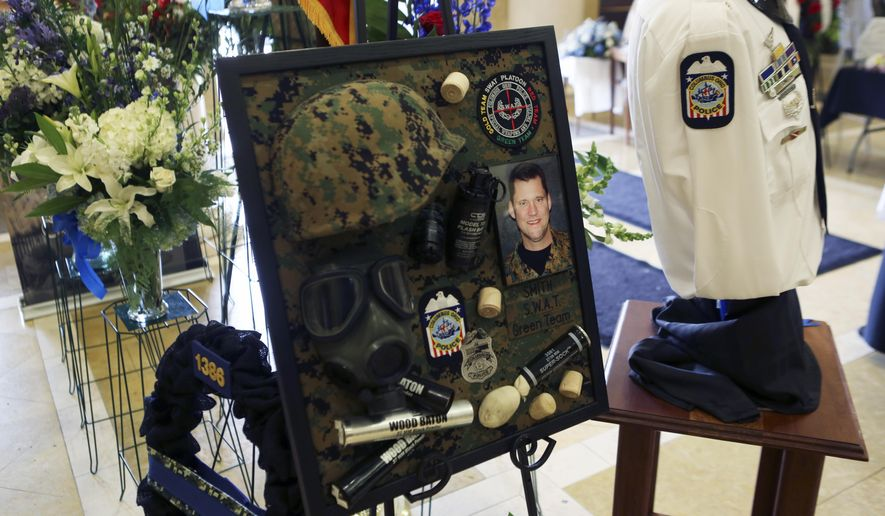 Memorabilia of  Columbus Police officer Steve Smith is displayed in the foyer of St. Paul Apostle Church in Westerville, Ohio, on Tuesday, April 19, 2016. Smith was shot during a April 10 standoff and died two days later.   (Eric Albrecht/The Columbus Dispatch via AP) MANDATORY CREDIT