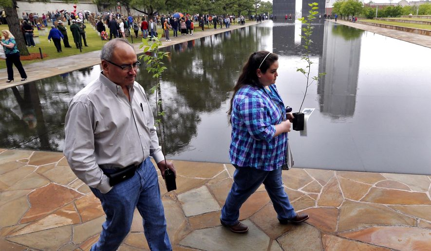 Louis Hernandez and daughter Sarah Hernandez carry seedlings from the Survivor Tree following the 21st anniversary remembrance ceremony for the Oklahoma City National Memorial Museum on Tuesday, April 19, 2016, in Oklahoma City, Okla. Sarah survived the bombing in the YMCA day care center across the street. (Steve Sisney/The Oklahoman via AP)