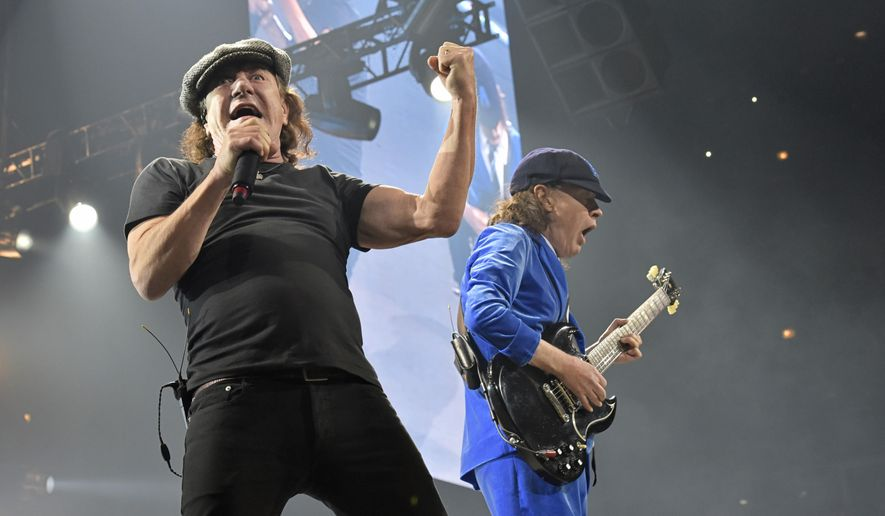 In this Feb. 17, 2016 file photo, Brian Johnson, left, and Angus Young perform with AC/DC on the Rock or Bust Tour in Chicago. (Photo by Rob Grabowski/Invision/AP, File)