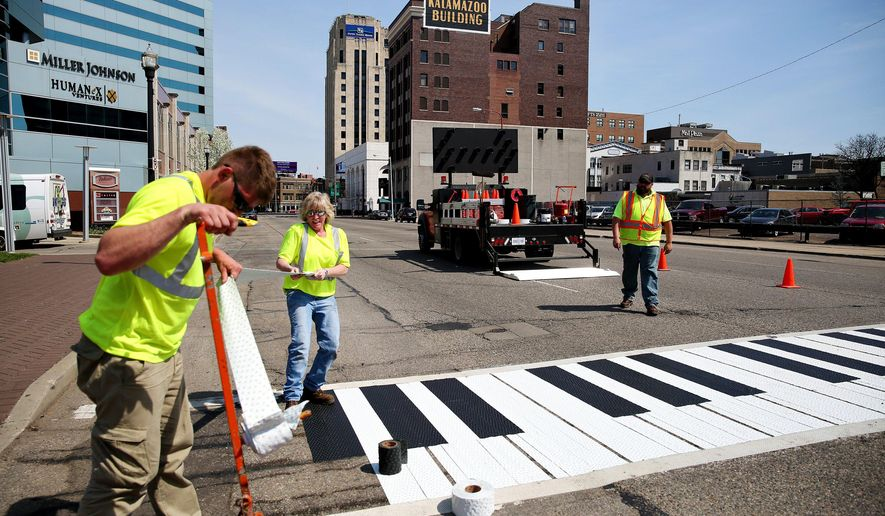 In this April 18, 2016, photo, Glen VanNortwick, Kim Weiss and Paul Keene work on a piano crosswalk in Kalamazoo, Mich. Some crosswalks in downtown Kalamazoo are being transformed to look like piano keys ahead of a big musical event that takes place April 26 to May 14. (Chelsea Purgahn/Kalamazoo Gazette-MLive Media Group via AP) LOCAL TELEVISION OUT; LOCAL RADIO OUT; MANDATORY CREDIT