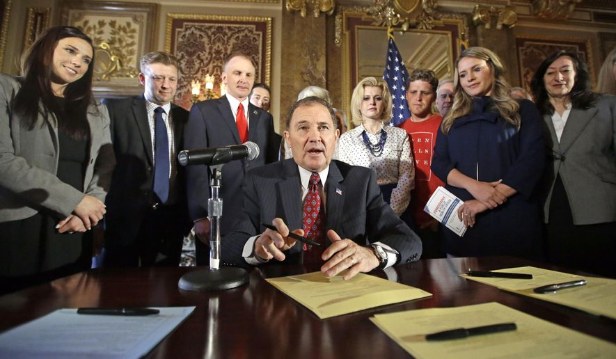 Utah Gov. Gary Herbert looks up during a ceremonial signing of a state resolution declaring pornography a public health crisis, Tuesday, April 19, 2016, in Salt Lake City. Herbert recognized it's a bold assertion but said Utah wants to take the lead sounding a voice of warning about the harms of pornography. (AP Photo/Rick Bowmer)
