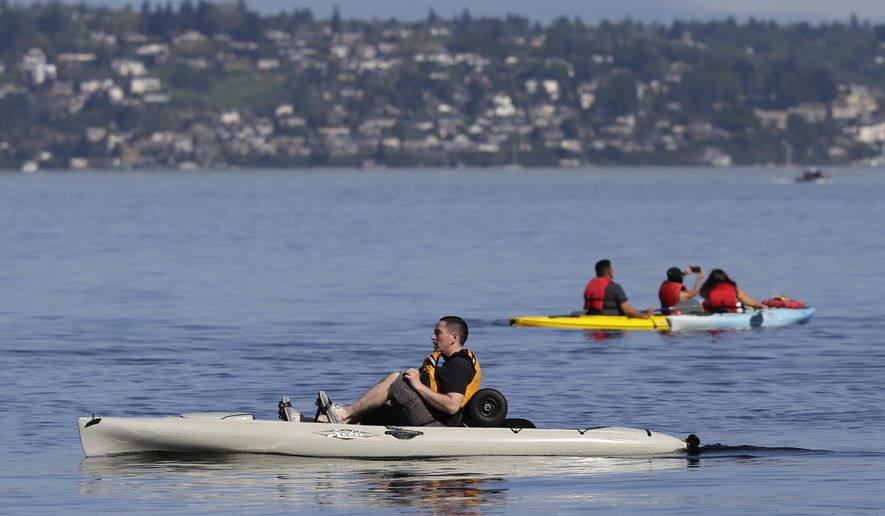 A kayaker in a pedal kayak, left, moves past a more traditional craft near Owen Beach in Point Defiance Park, Monday, April 18, 2016, in Tacoma, Wash. Temperatures were at record levels in Western Washington Monday. (AP Photo/Ted S. Warren)