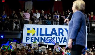 Protesters hold up signs as Democratic presidential candidate Hillary Clinton speaks at a campaign stop, Wednesday, April 20, 2016, in Philadelphia. (AP Photo/Matt Rourke)