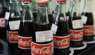 FILE - In this July 9, 2015, file photo, bottles of Coca-Cola are on display at a Haverhill, Mass., supermarket. On Wednesday, April 20, 2016, Coca-Cola Co., reports financial results. (AP Photo/Elise Amendola, File)
