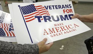 Supporters grab signs as they arrive to hear Republican presidential candidate Donald Trump speak during a campaign stop, Wednesday, April 20, 2016, in Indianapolis. (AP Photo/Darron Cummings)