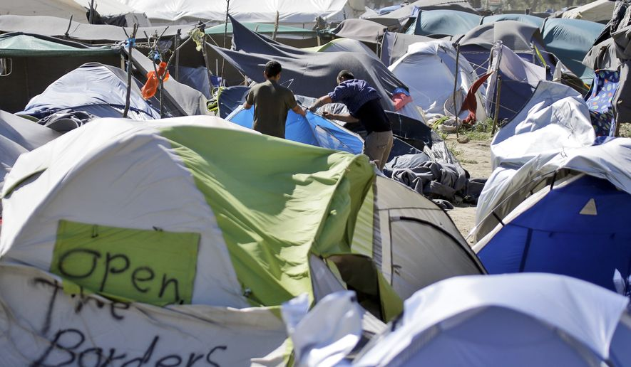 """Two men set a tent at a camp for migrants and refugees at the northern Greek border point of Idomeni, Greece, Wednesday, April 20, 2016. Human Rights Watch says the initial round of deportations of migrants from Greece to Turkey under a new European Union-Turkey deal were """"rushed, chaotic and violated the rights of those deported."""" (AP Photo/Gregorio Borgia)"""