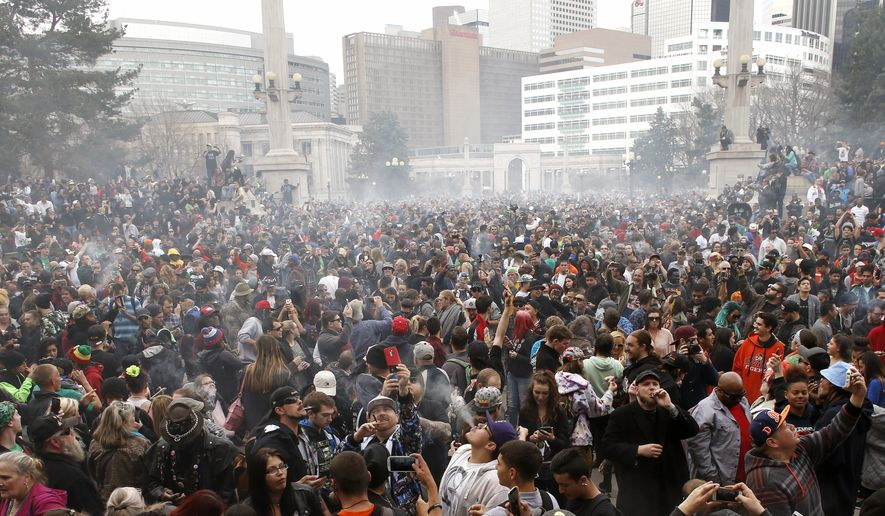 A gathered crowd smokes marijuana en masse — as per tradition at 4:20 p.m. — during the annual 4/20 marijuana gathering at Civic Center Park in downtown Denver, Wednesday, April 20, 2016. (AP Photo/Brennan Linsley)