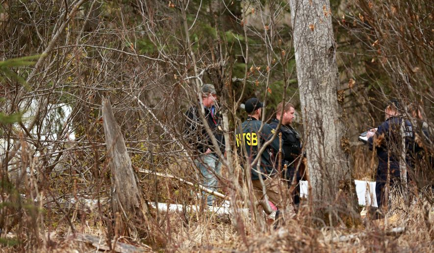 Investigators examine the scene of a fatal airplane crash Wednesday, April 20, 2016, off Beach Lake Road near Chugiak, Alaska outside Anchorage. Four people were killed Wednesday when a small airplane crashed just north of Anchorage, the fire chief said. (Loren Homes/Alaska Dispatch News via AP)  KTUU-TV OUT; KTVA-TV OUT; THE MAT-SU VALLEY FRONTIERSMAN OUT; MANDATORY CREDIT