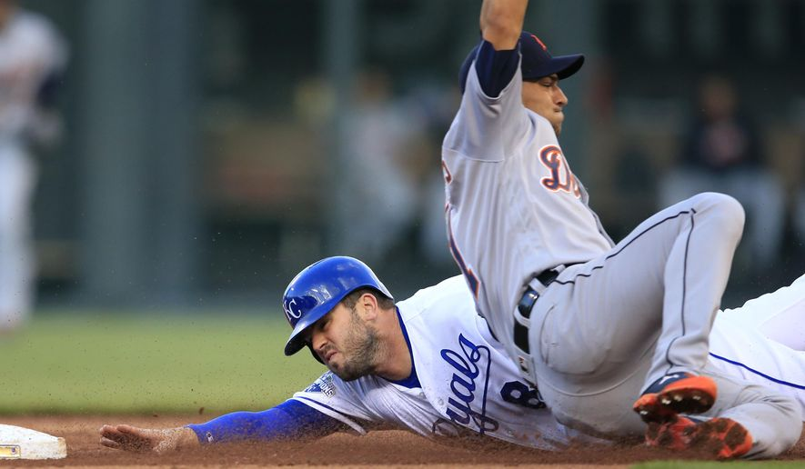 Kansas City Royals' Mike Moustakas (8) is tagged out by Detroit Tigers shortstop Jose Iglesias during the third inning of a baseball game at Kauffman Stadium in Kansas City, Mo., Wednesday, April 20, 2016. Moustakas was caught stealing on the play. (AP Photo/Orlin Wagner)