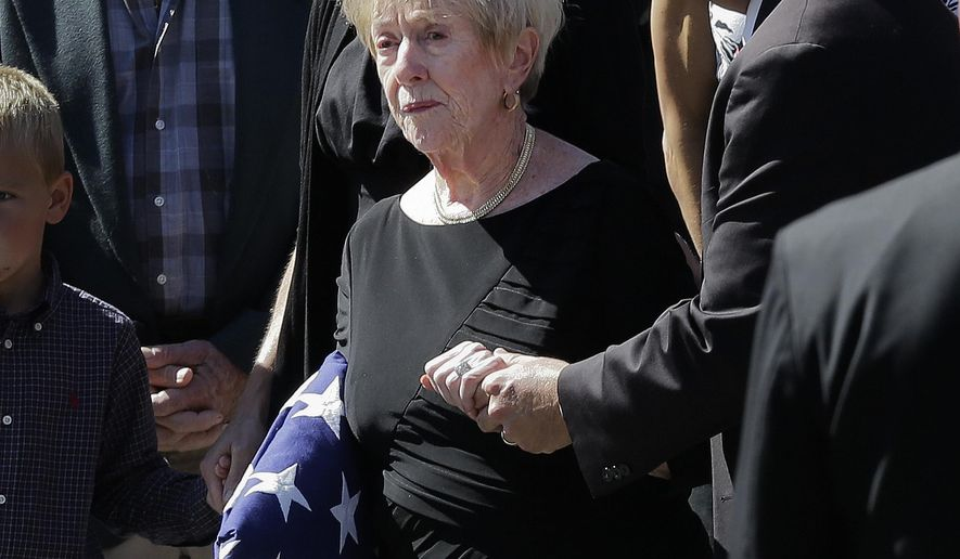 """FILE - In this Sept. 19, 2012, file photo photo, Barbara Doherty, mother of slain former Navy SEAL Glen Doherty, is escorted from the Church of St. Eulalia in Winchester, Mass., after his funeral. Doherty was a CIA operative killed in the 2012 attack on a U.S. diplomatic facility in Benghazi, Libya. His mother says the spy agency has agreed to pay a death benefit even though his parents were not entitled under a standard federal insurance policy he held that pays a survivor benefit only to spouses and dependents. Barbara Doherty, on April 20 called the expanded benefit """"symbolic justice."""" (AP Photo/Elise Amendola, File)"""