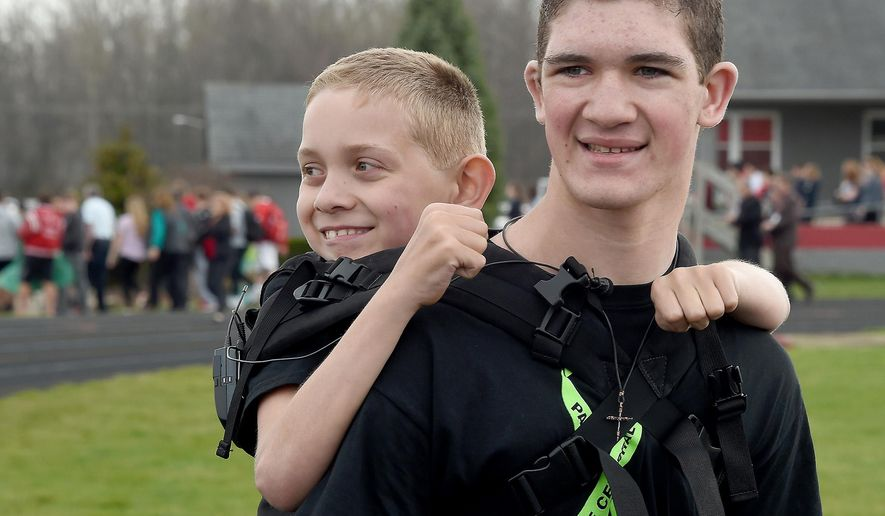 Hunter Gandee, 16, and his brother Braden, 9, start their third Cerebral Palsy Swagger walk at Bedford Community Stadium Wednesday at Bedford High School are cheered on as they leave. The walk is 111 miles and will end at the Capitol in Lansing, Mich., Monday, April 25.  Hunter Gandee will carry Braden for the entire walk to bring more awareness to Cerebral Palsy, but this year Braden will walk the last half mile to the Capitol. (Tom Hawley/The Monroe News via AP)