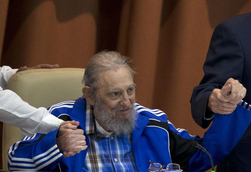 Fidel Castro sits as he clasps hands with his brother, Cuban President Raul Castro, right, and second secretary of the Central Committee, Jose Ramon Machado Ventura moments before the playing of the Communist party hymn during the closing ceremonies of the 7th Congress of the Cuban Communist Party, in Havana, Cuba, Tuesday, April 19, 2016. Fidel Castro formally stepped down in 2008 after suffering gastrointestinal ailments and public appearances have been increasingly unusual in recent years. (Ismael Francisco/Cubadebate via AP)