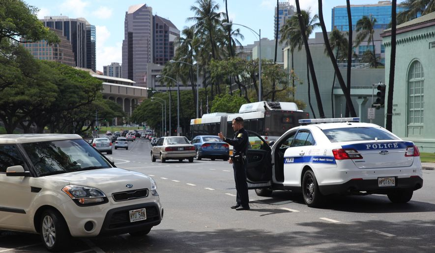 A Honolulu police officer directs traffic on a downtown street on Wednesday, April 20, 2016 in Honolulu. Hawaii lawmakers are considering a bill to clarify the public's right to photograph or film police officers as long as it doesn't interfere with law enforcements' duties. (AP Photo/Marina Riker)