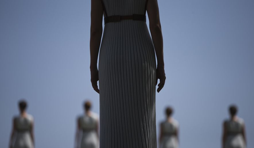 High Priestess Katerina Lehou stands in front of a line of priestesses during the dress rehearsal for the lighting of the Rio Olympics flame, in Ancient Olympia, southern Greece, on Wednesday, April 20, 2016. The meticulously choreographed ceremony will be repeated Thursday in the ruined birthplace of the ancient Olympics in southern Greece, in the presence of top International Olympic Committee and Rio organizing officials. That will touch off a relay that will conclude with the Rio Games opening ceremony in August. (AP Photo/Petros Giannakouris)