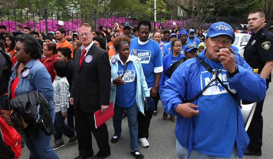 Action Now member Ellyson Carter, right, of Chicago, uses a megaphone to lead a rally of fellow members protesting in front of the Executive Mansion in Springfield , Ill., as part of their Lobby Day for Fair Tax on Wednesday, April 20, 2016. The protestors were part of a larger coalition including Chicago Teachers Union members, other union members and community groups from throughout the state organized through The Grassroots Collaborative of Chicago fighting for education and public service funding impacted by the lack of a state budget. (David Spencer/The State Journal-Register via AP)  NO SALES, MANDATORY CREDIT